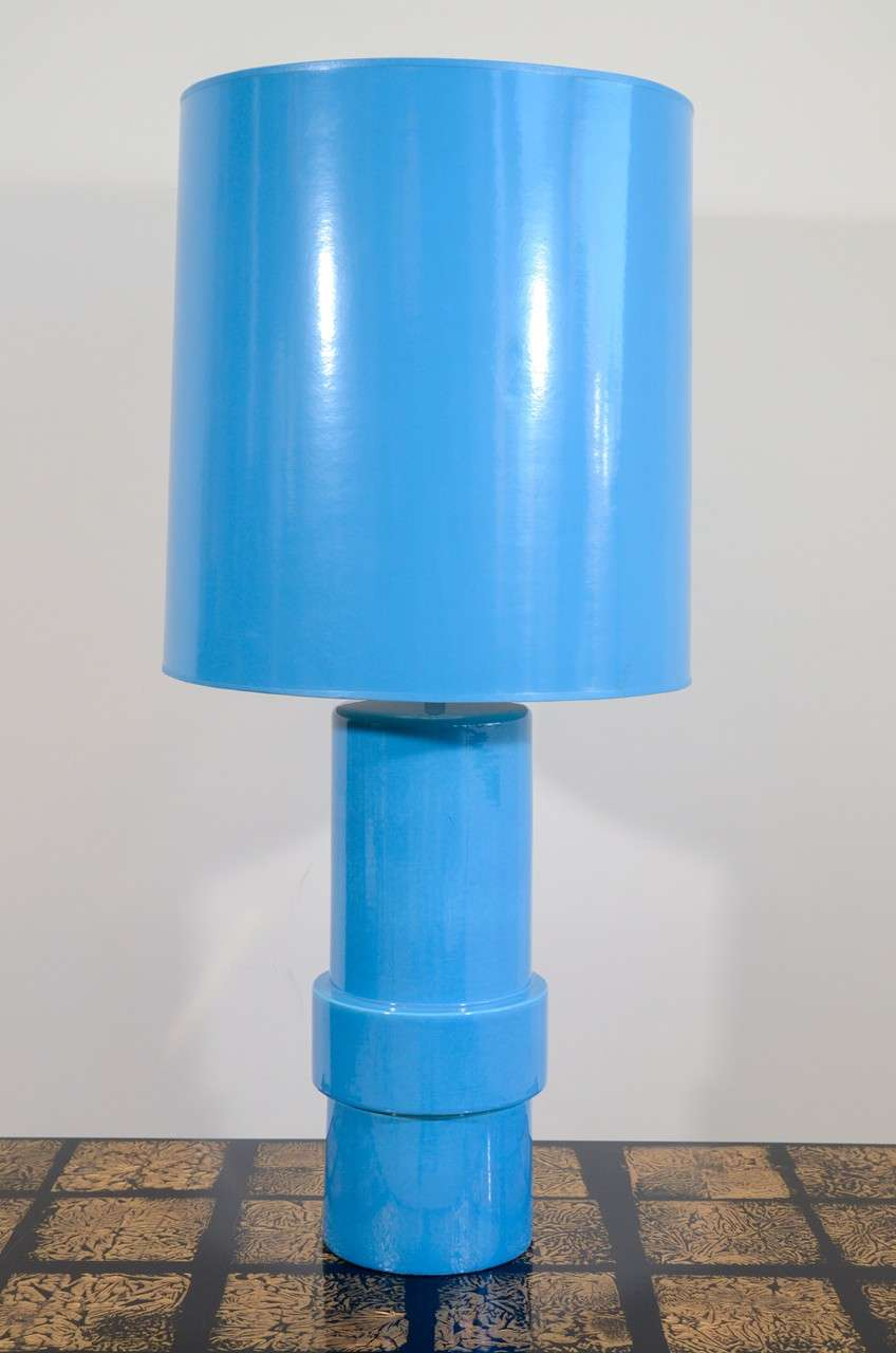 The slip cast ceramic cylindrical body with a raised band towards the base, covered with a blue glaze, with matching cylindrical shade.