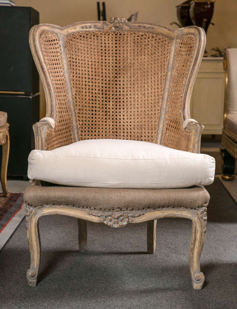 Pair of vintage French Louis XV style caned wingback bergère chairs, circa 1930s, stunning and impossible to find! In original distressed finish with a touch of grey, the slightly domed back flanked by winged sides and padded arms, the back