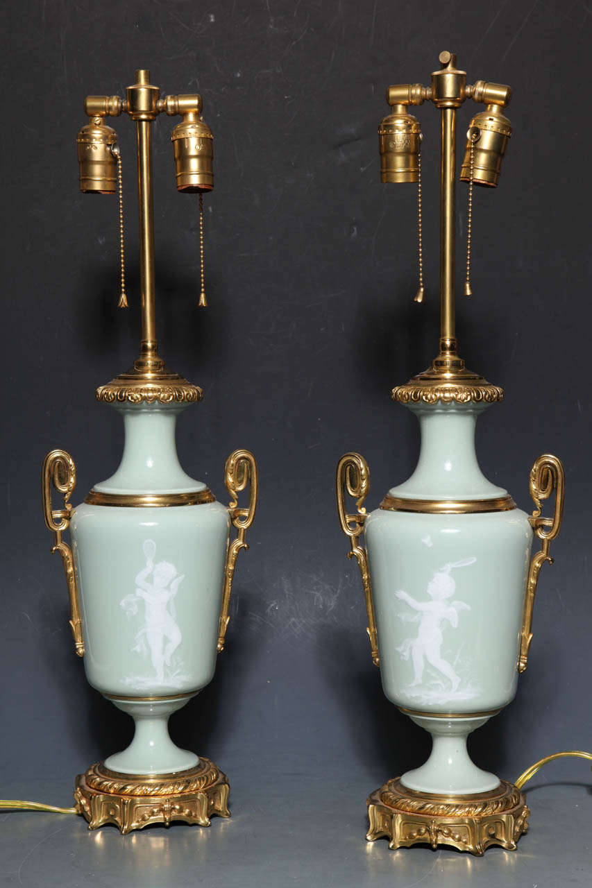 A Magnificent pair of 'pate sur pate' (paste on paste) decorated vases with lavish gilt bronze mounts. This method of decoration was perfected by Marc Louis Solon at Sevres circa 1850. He later moved to England where under his direction Minton's