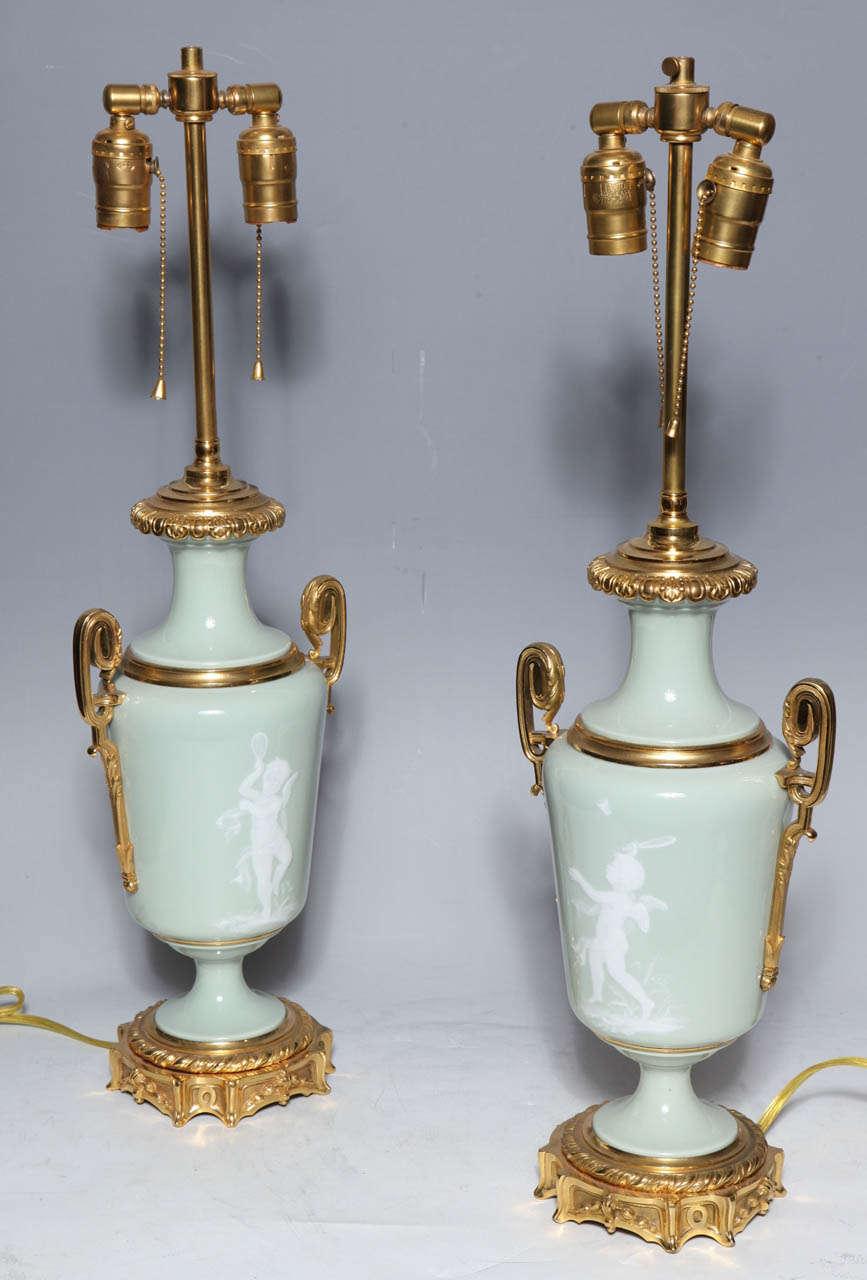 British Pair Ormolu Mounted 'Pate sur Pate' Porcelain Lamps Depicting Cupids For Sale