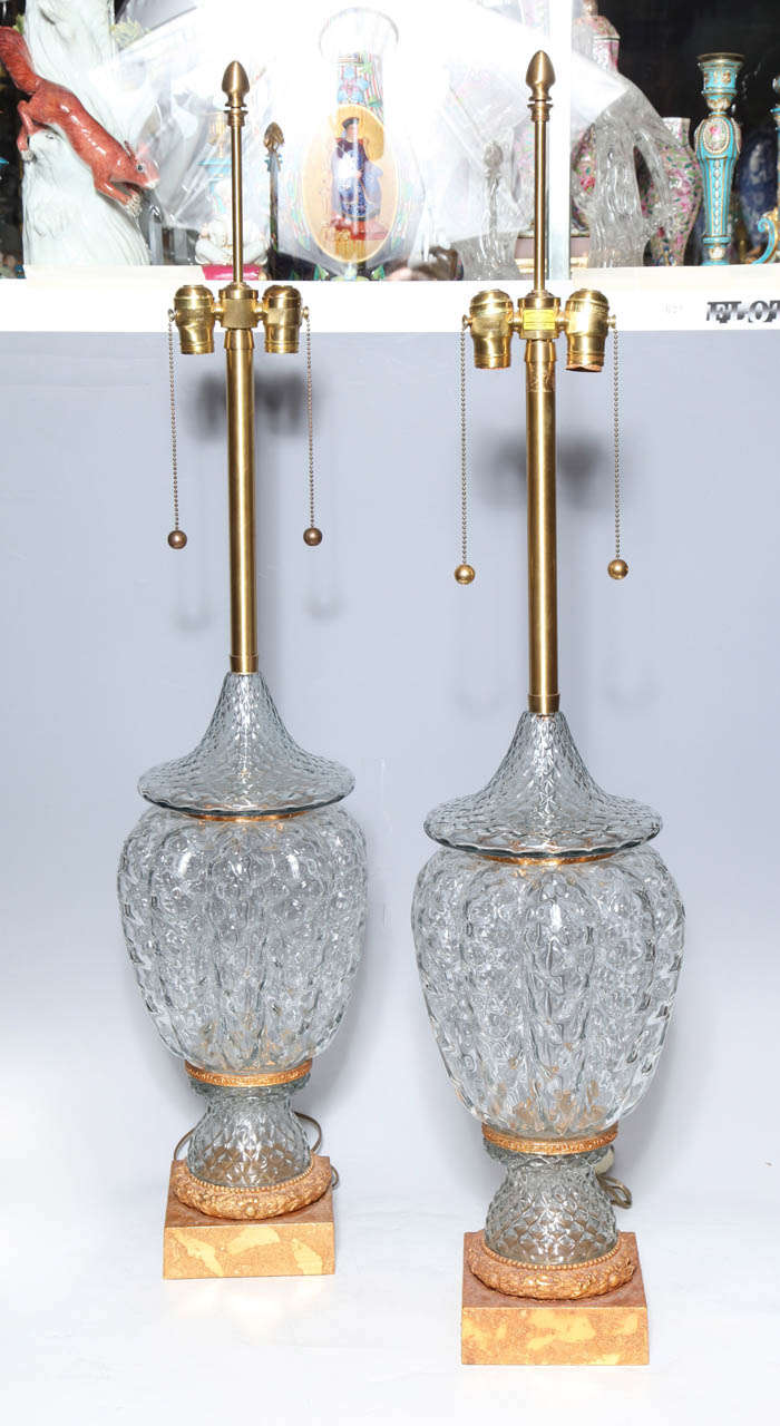 A monumental pair of murano glass vases wired as lamps with gilt bronze mounts. On a small island in the Venetian lagoon, Murano, artists make magic with common materials and great artistry. While it is believed that glass making started in the 8th
