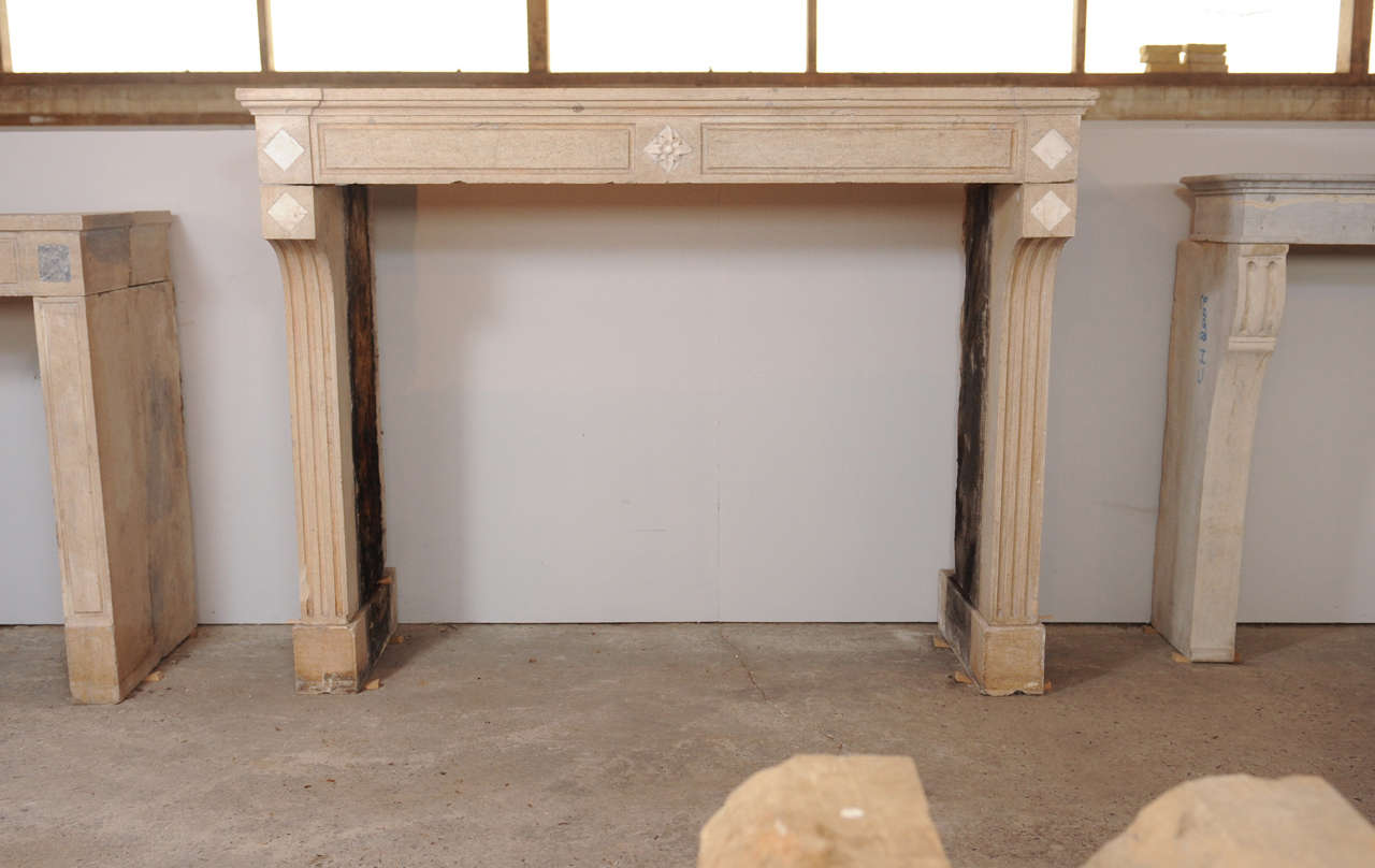 an early 19th c french neoclassical carved limestone fireplace