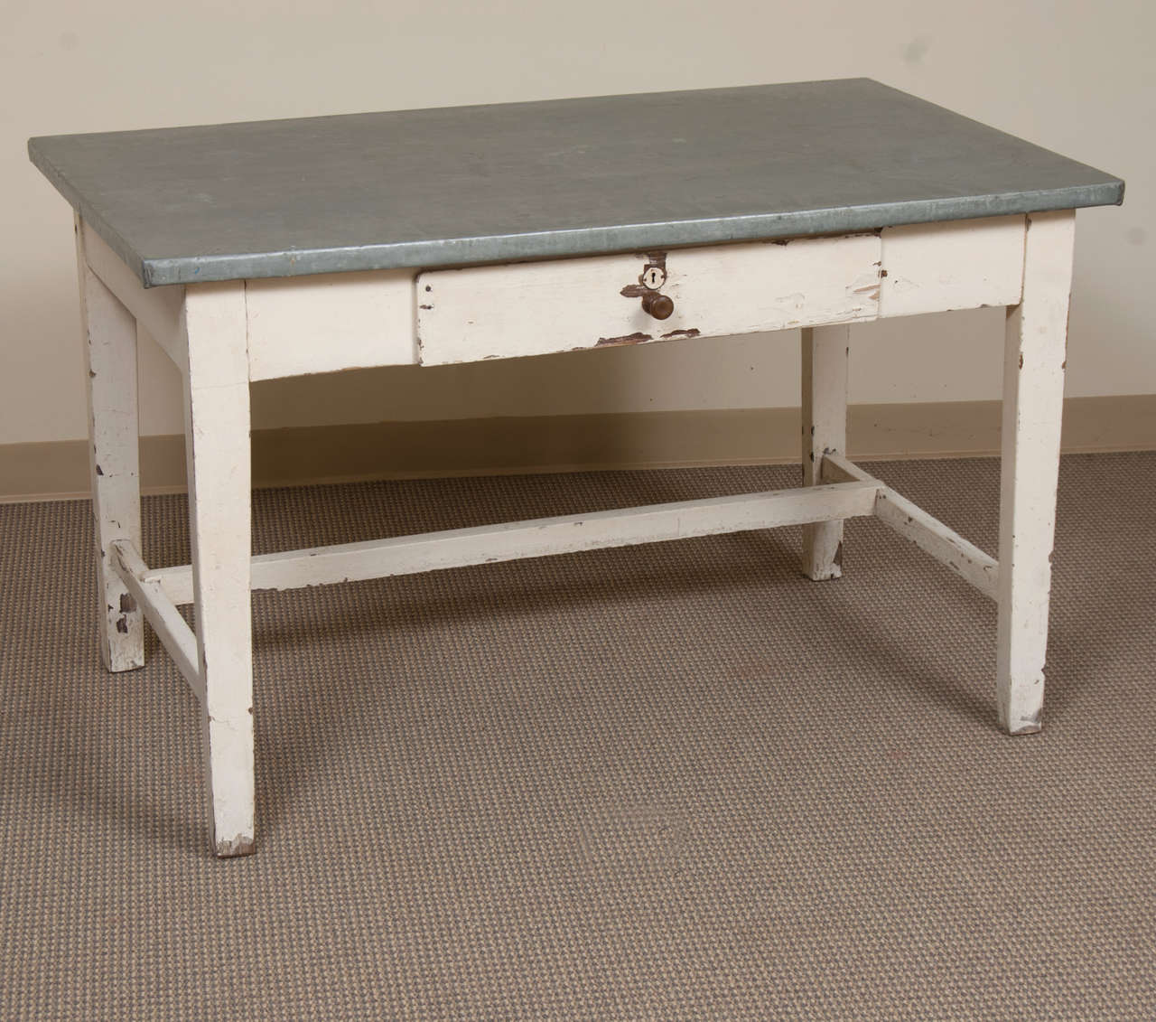 A sturdy and utilitarian pine and oak writing or work table featuring a zinc top in excellent condition, a single central drawer and an off-centre stretcher to the distressed white-painted base.