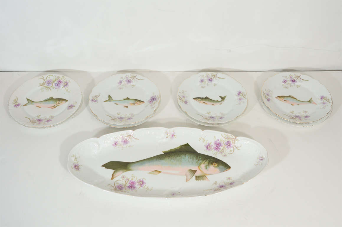 This handsome porcelain dining set features a large rectangular platter with 8 smaller round dessert/serving plates. Each piece features a European chub fish in the center of dish replete with shades of moss, rose and sky blue. There is a floral