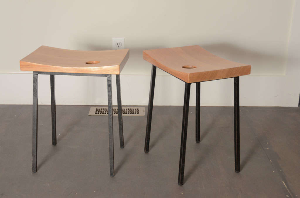 Modernist french stools with curved wooden tops that have a circle detail carved from the top. black metal legs.