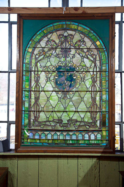 Beautiful large antique stain glass window.  Decorative piece with shield motif in center of panel.