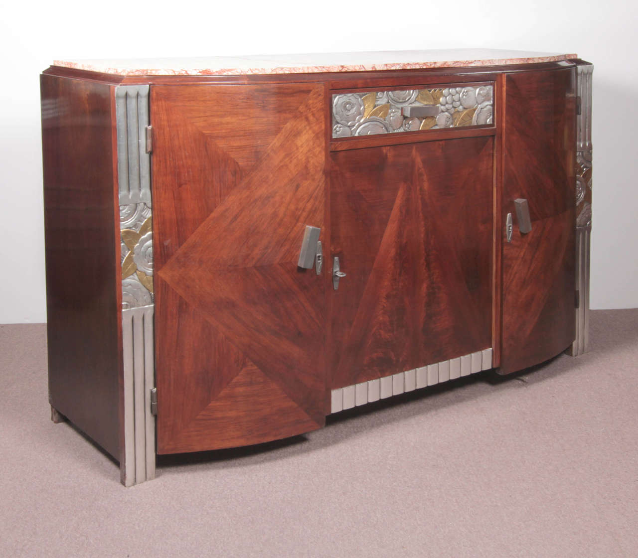Original French Art Deco carved and inlaid three door cabinet. Beautifully crafted parquetry inlaid doors create a central pyramidal form amidst geometric shapes. The top drawer features a hand carved gold and silver leaf frieze with stylized floral