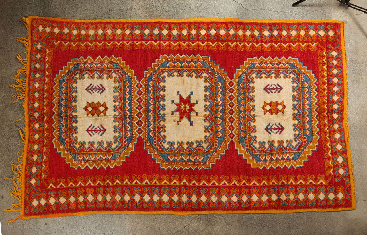 Vintage Berber rug from the Taznakht tribe in south eastern Morocco.  Rare piece with beautiful color combination in organic dyes and lamb wool. Stunning vintage Moroccan tribal rug, hand- woven by the Berber women of Morocco. Orange field with red