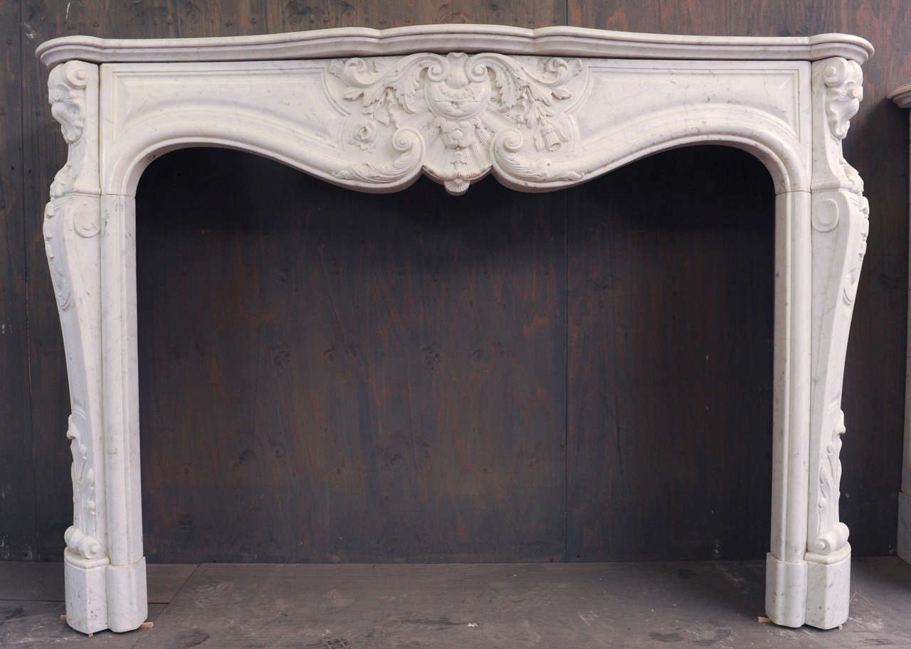 View this item and discover similar fireplaces and mantels for sale at 1stdibs - A 19th century French richly carved white Carrara marble fireplace / mantel piece in Rococo style. Measurements: 107.5 cm. high x 155.5 cm. wide x 35