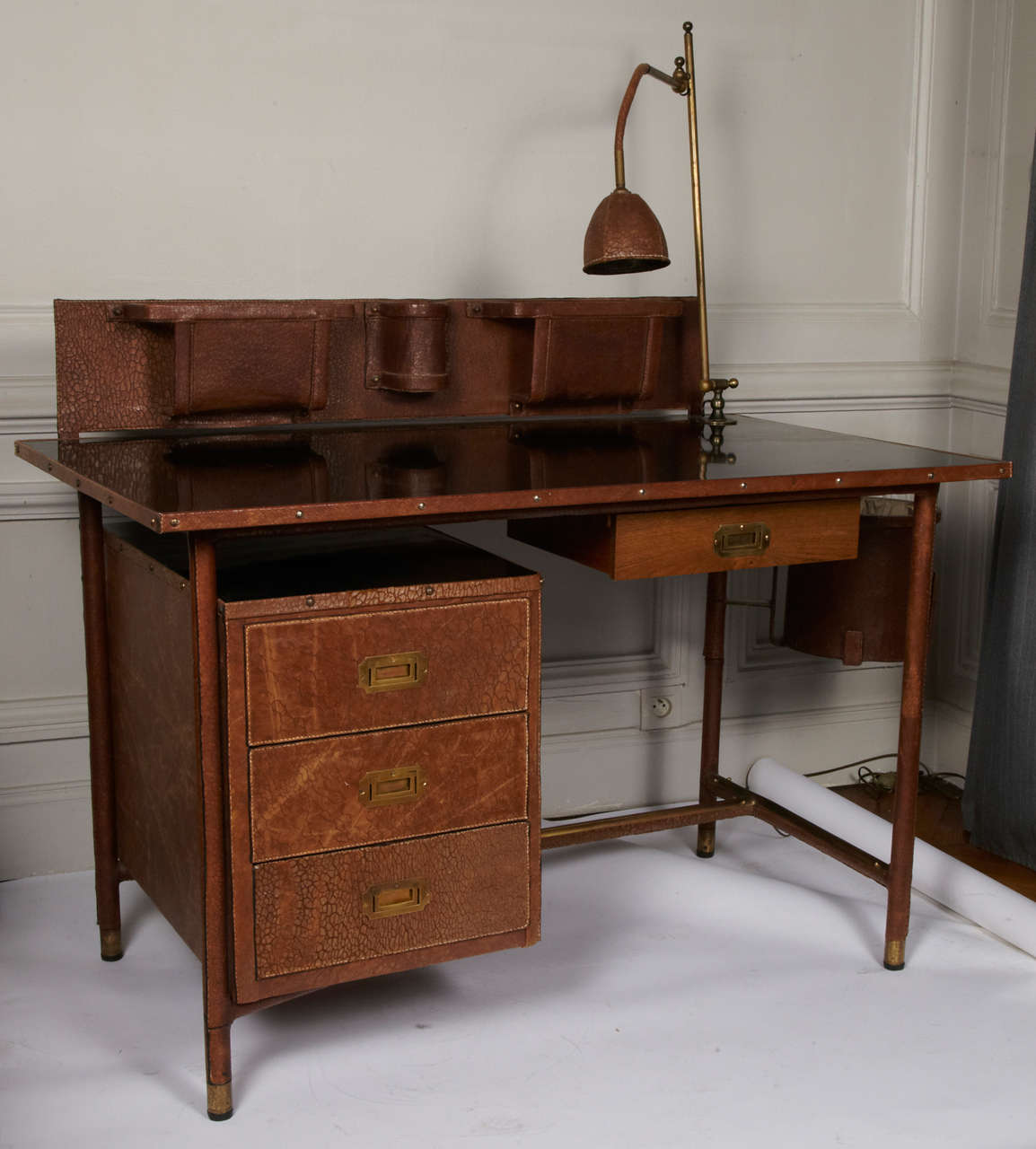 Rare Jacques Adnet desk with lamp, book rack and bin.