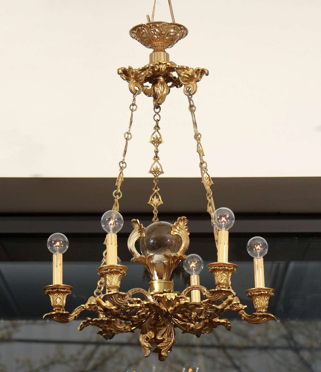 Beautifully detailed six-arm chandelier highlighted with large crystal orb.