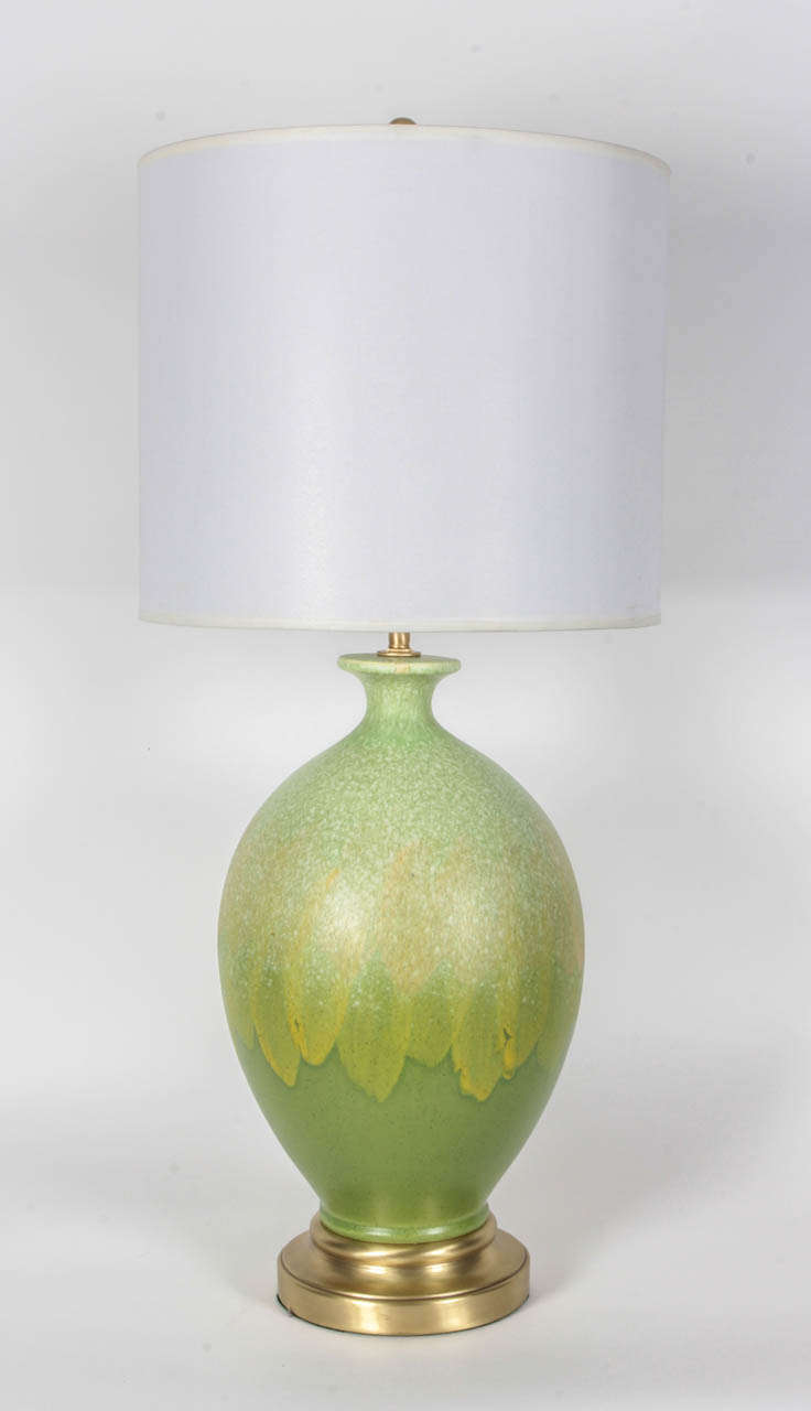 Mid-Century pair of vibriant green matte glazed ceramic lamps with a slightly speckled finish with satin brass bases. Lamps feature double pull chain sockets and new wiring.