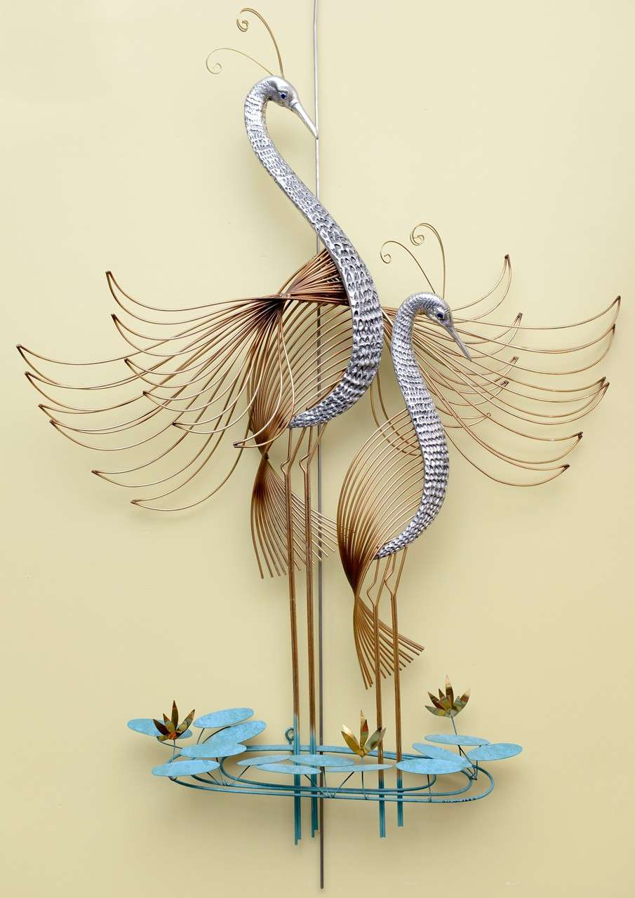 Stunning C. Jeré wall sculpture of two birds of paradise or peacocks with wings spread standing amongst water ripples and water lilies. With mixed metals and patinas brass, nickel and verdegris. Wonderfully worked metal sculpture. Signed and