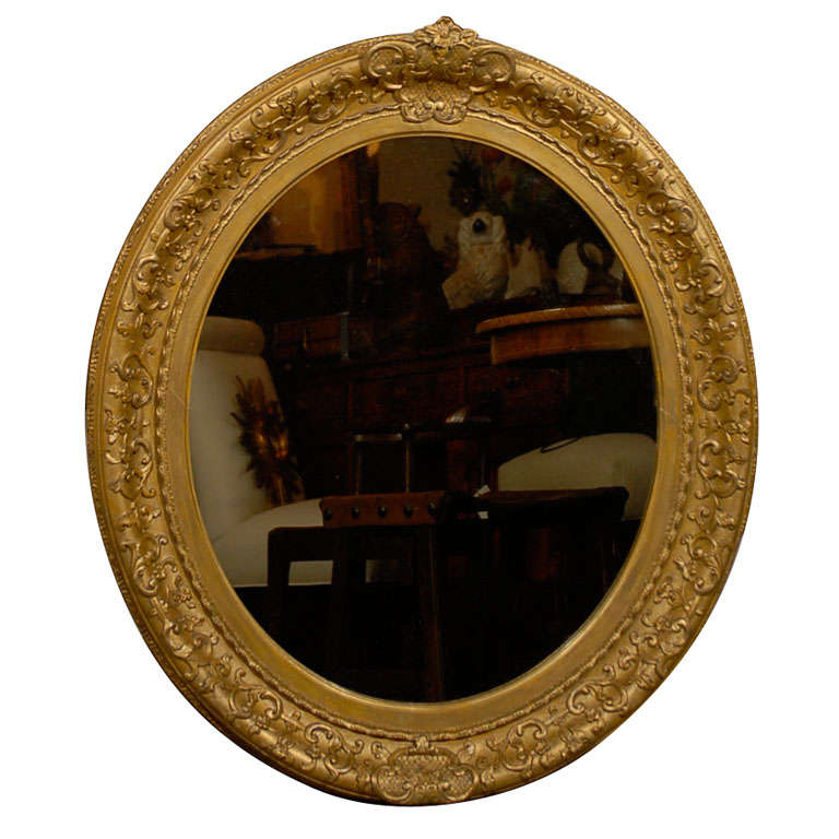 English 1870s Oval Giltwood Carved Mirror with Floral Arabesques and Small Crest