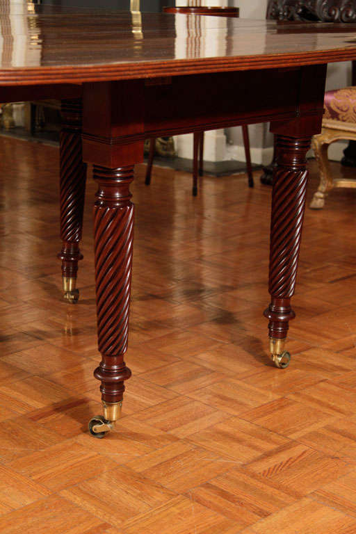 An Irish Regency mahogany extending dining table on turned twisted legs on casters. 