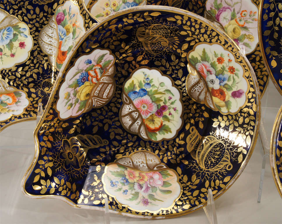 An extraordinary, museum quality botanical and mollusk decorated dessert service. Each uniquely decorated piece is hand painted with all different shells and flowers on a cobalt blue ground, all highlighted in gold. There are 12 dessert plates, 2