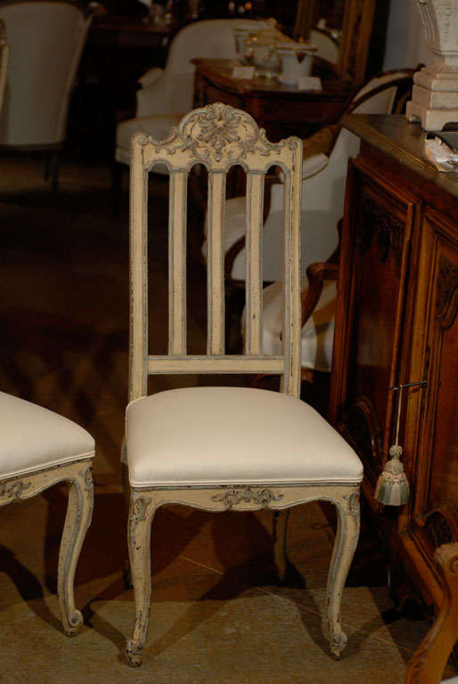 A set of six Belgian Rococo style dining room side chairs from the mid-19th century with carved crests and new upholstery. Each of this set of Belgian side chairs features a lathed back, surmounted by an exquisite carved crest, adorned with Rocaille