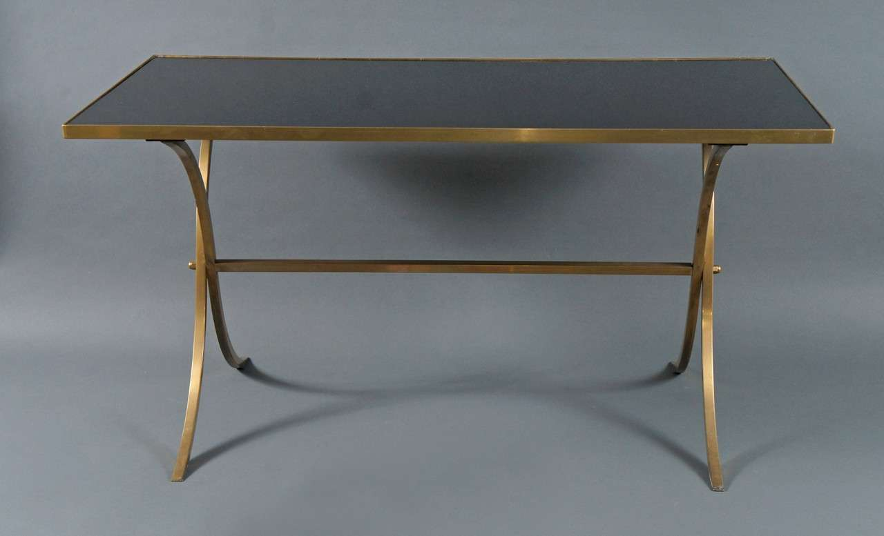 Brass coffee table with black top.