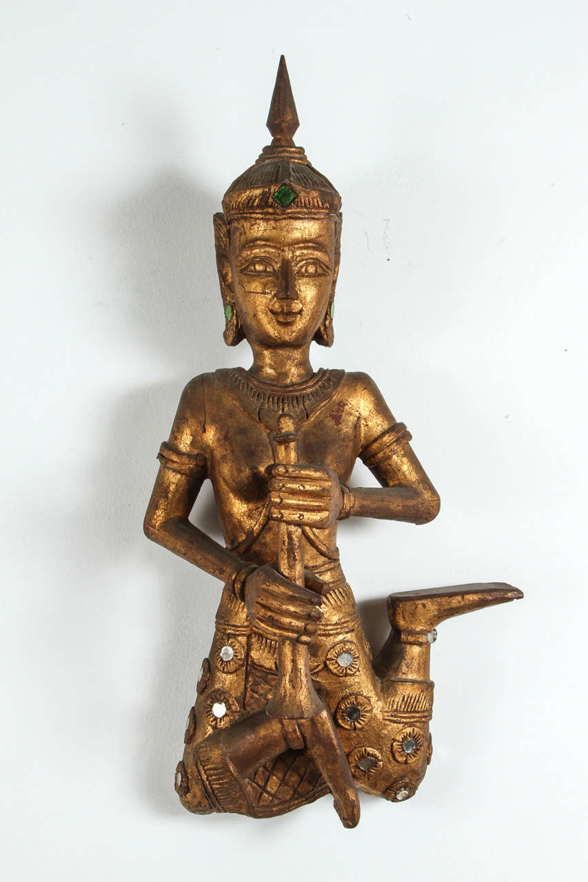Large pair of Thai figures of Siamese musicians, nicely carved. Musicians in seated are holding a flute, gilt over red lacquer that can be seen in the back.  Gold gilt adorned with green and clear mirrored gem pieces to reflect the light. Brass