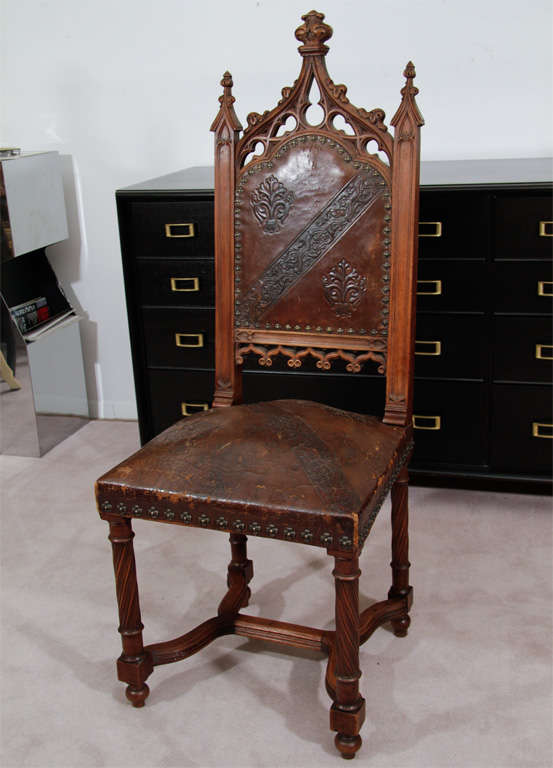 A pair of gothic chairs in hand carved wood with tooled leather backs and seats. The seatbacks have a stylized vegetal motif and the seats and backs have cruciform nail head detailing.