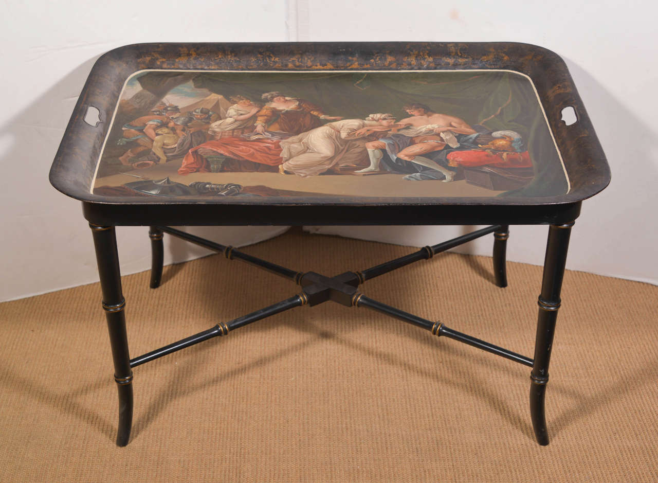 Continental tole tray on stand of rectangular handled form, tray decorated with polychrome classical figures on black ground, on ebonized wood stand.