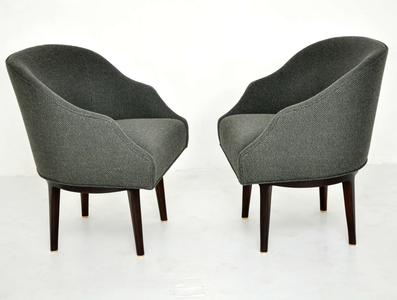 Pair of swivel lounge chairs by Edward Wormley for Dunbar. Fully restored. Dark espresso finish frames with new woven charcoal upholstery. Chairs have a swivel and return mechanism.