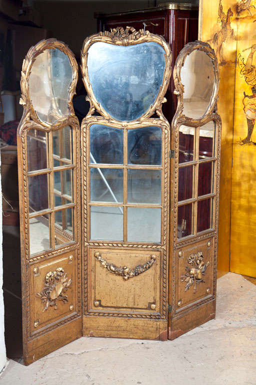 Three panel Louis XVI style folding screen or room separator. Gilt gold finish having six small mirrors above finely carved panels. Reverse is upholstered in silk.