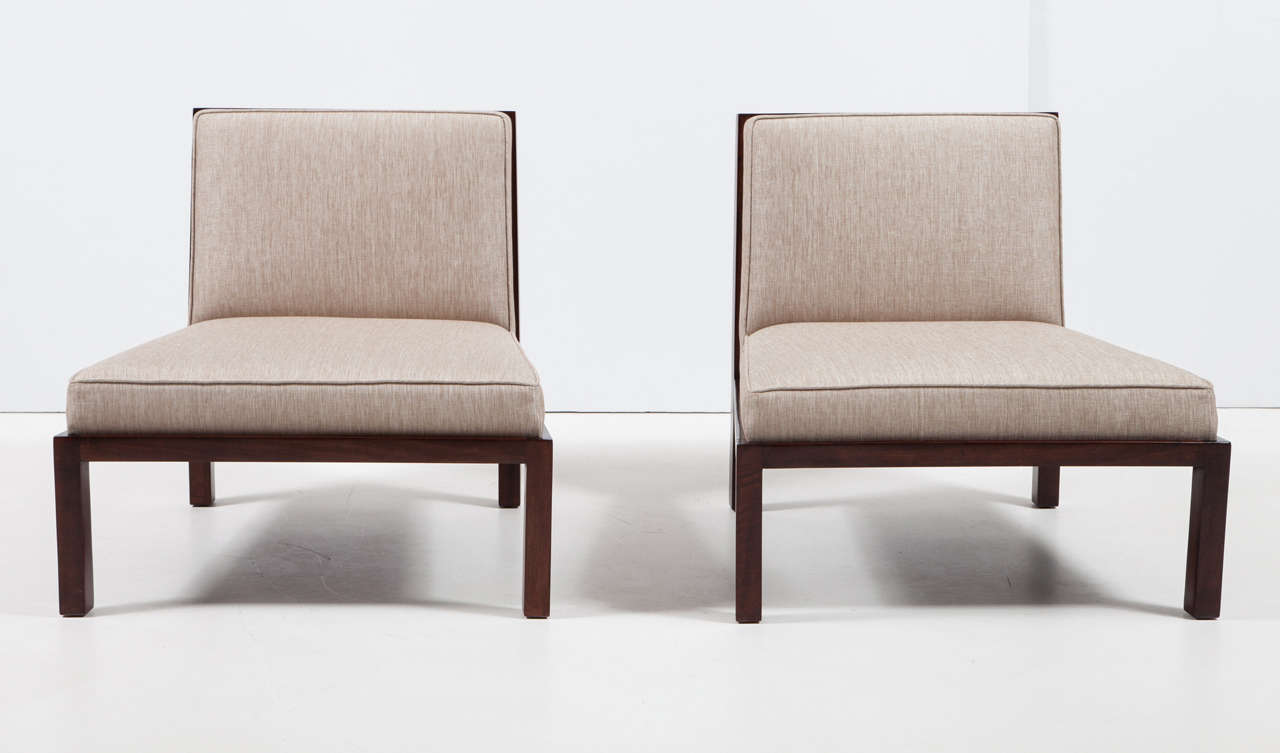 Pair of sleek stylish slipper chairs with walnut frames and upholstered in a linen fabric with a slight gold metallic thread. Chairs feature an open lattice back signature design detail.