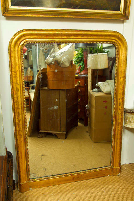 An exceptionally large Louis Philippe wall mirror with a giltwood frame. The frame is accented with a vine and leaf decoration.