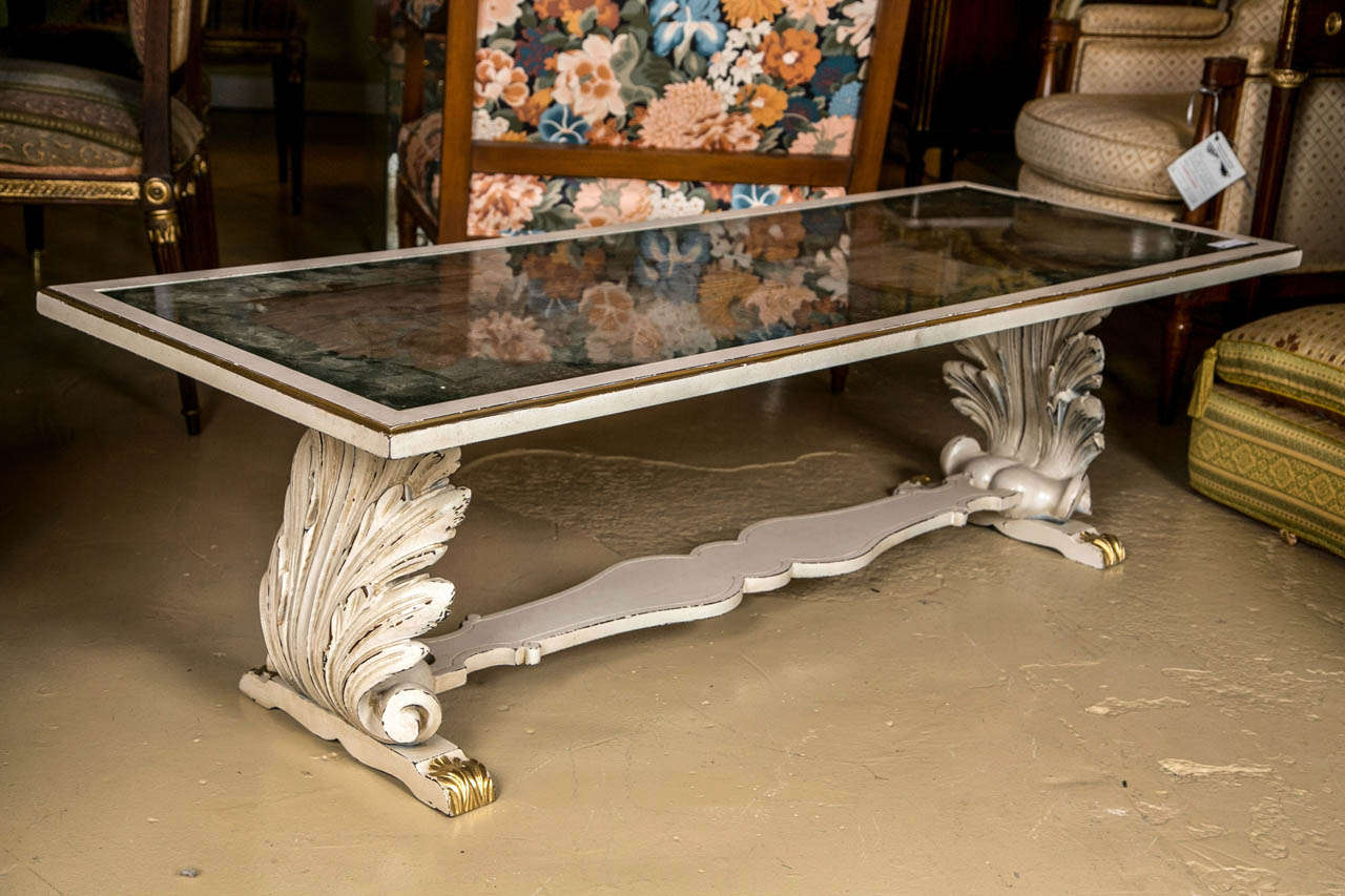 An Verne églomisé top coffee table attributed to Jansen. A finely decorated Verne églomisé shell and leaf design glass top coffee table. The base having a pair of shell carved distressed paint decorated carvings supported by a curved under support