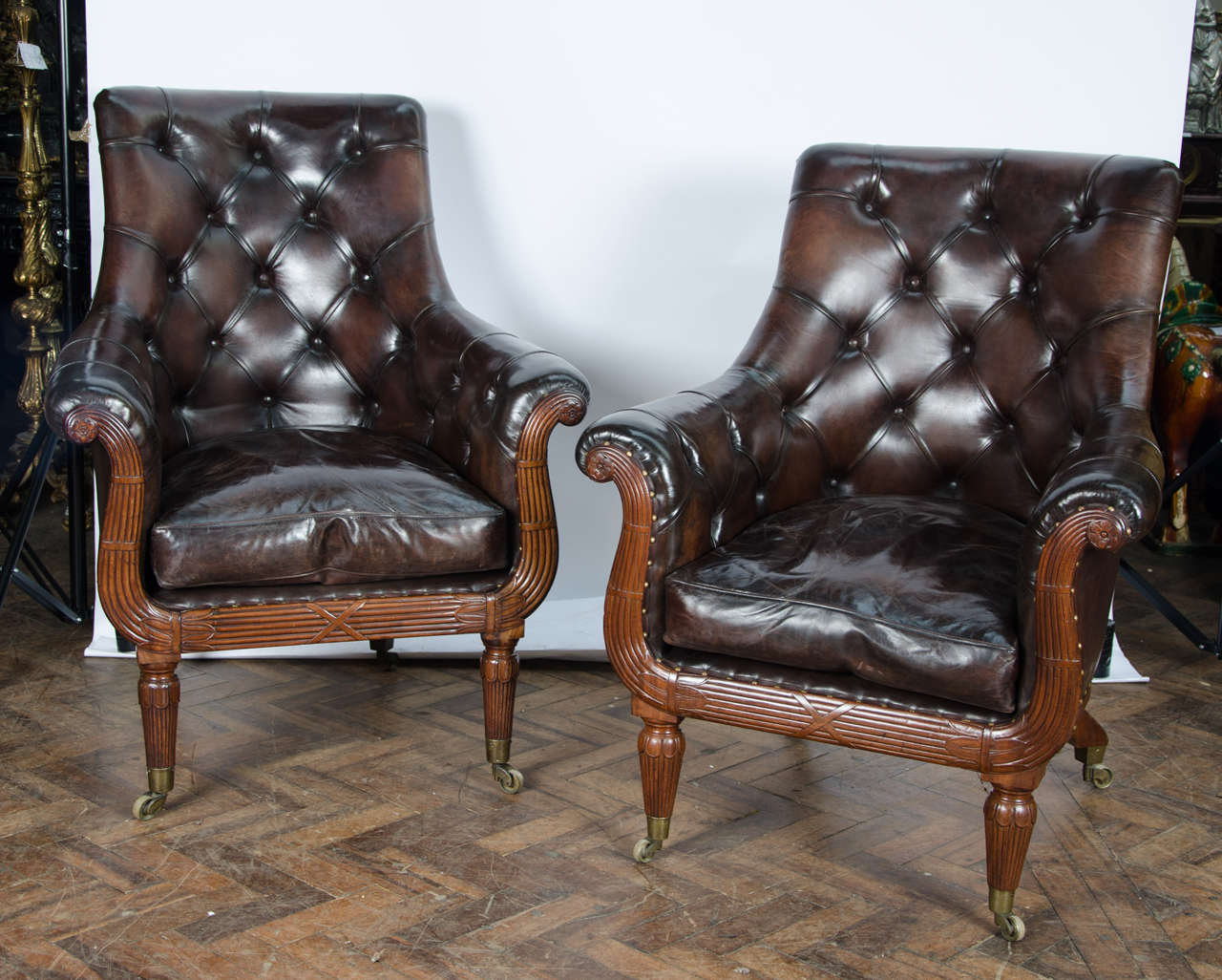 A very good quality pair of early 19th century mahogany library chairs, upholstered in deep button hide. The lyre shape having reeded carved decoration, raised on turned tapering legs, terminating in the original brass cup castors.