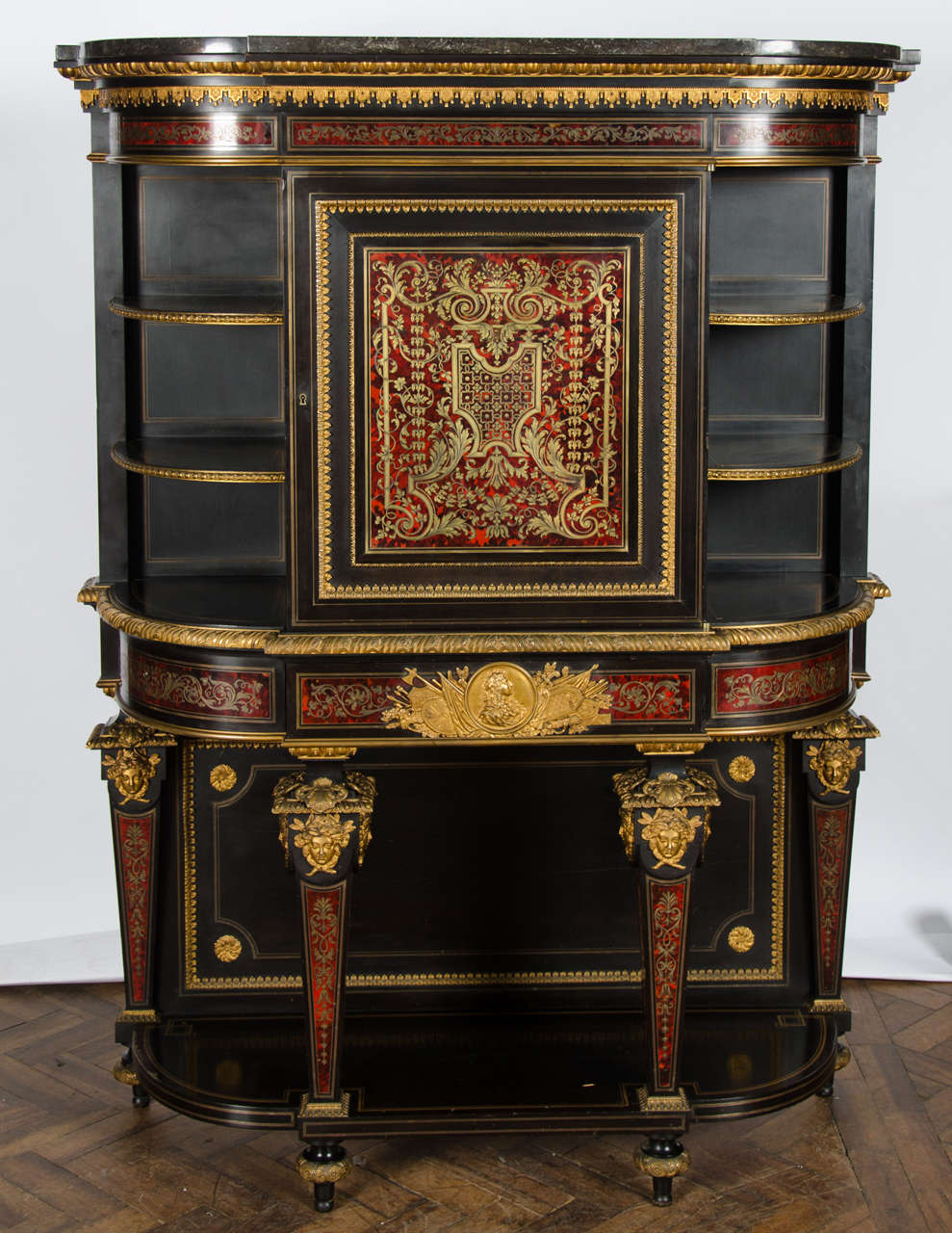 A fine quality French Louis XIV style Boulle inlaid bow fronted side cabinet, having a marble top, open shelves either side of the finely inlaid central door. A single frieze drawer with a gilded ormolu mount depicting the bust of Louis XIV. Raised