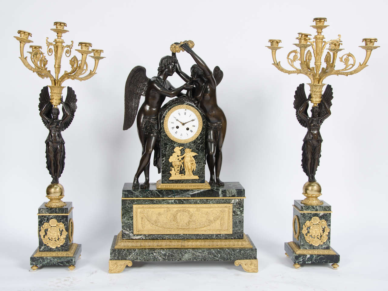A very impressive French gilded ormolu, bronze and marble clock garniture in the Empire style, having a pair of five-branch candelabra to either side of the clock. The clock having classical winged lovers, ormolu decoration set on green marble and