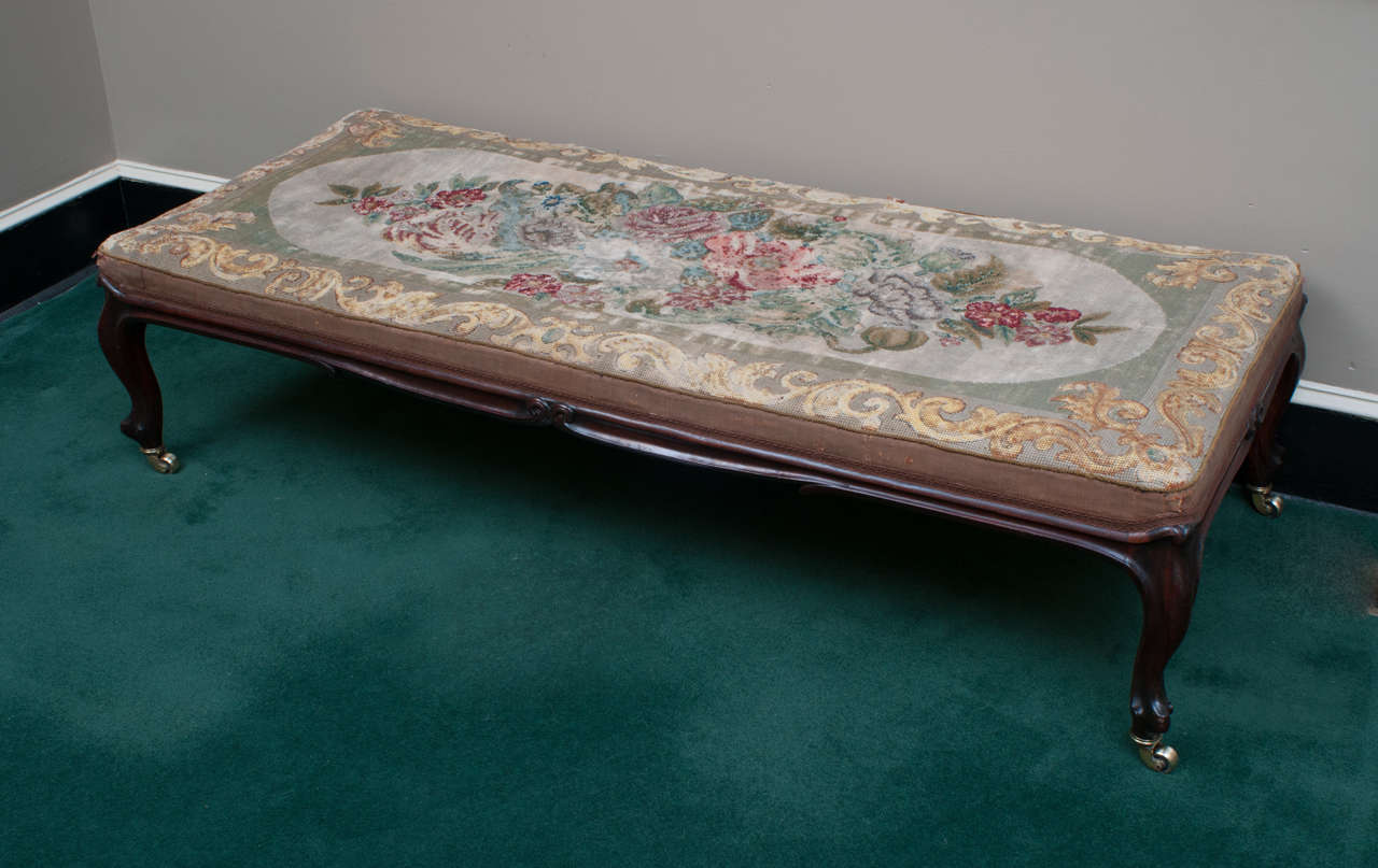 We don't know if the needlepoint upholstery on this bench is original, but it is certainly very old and beautiful, its worn condition gives the piece a patina and genuineness that cannot be copied. This sturdy bench is unusually wide and is