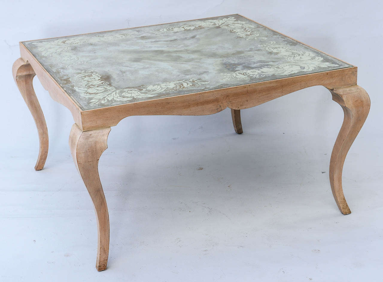 Coffee table, having eglomise (reverse painted) top with scrolling floral designs, raised on pickled wood stylized cabriole legs.
