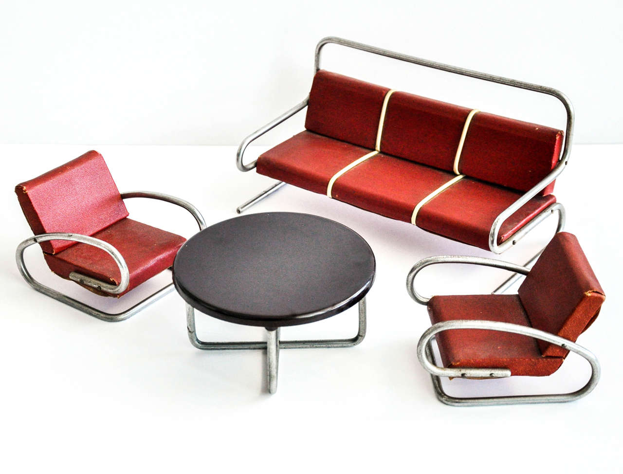 A four-piece set of miniature tubular furniture attributed to the Czech designer Jindrich Halabala (1903-1973). Halabala was a modernist Czech furniture designer who created functional, modular and affordable furniture that is prized today by