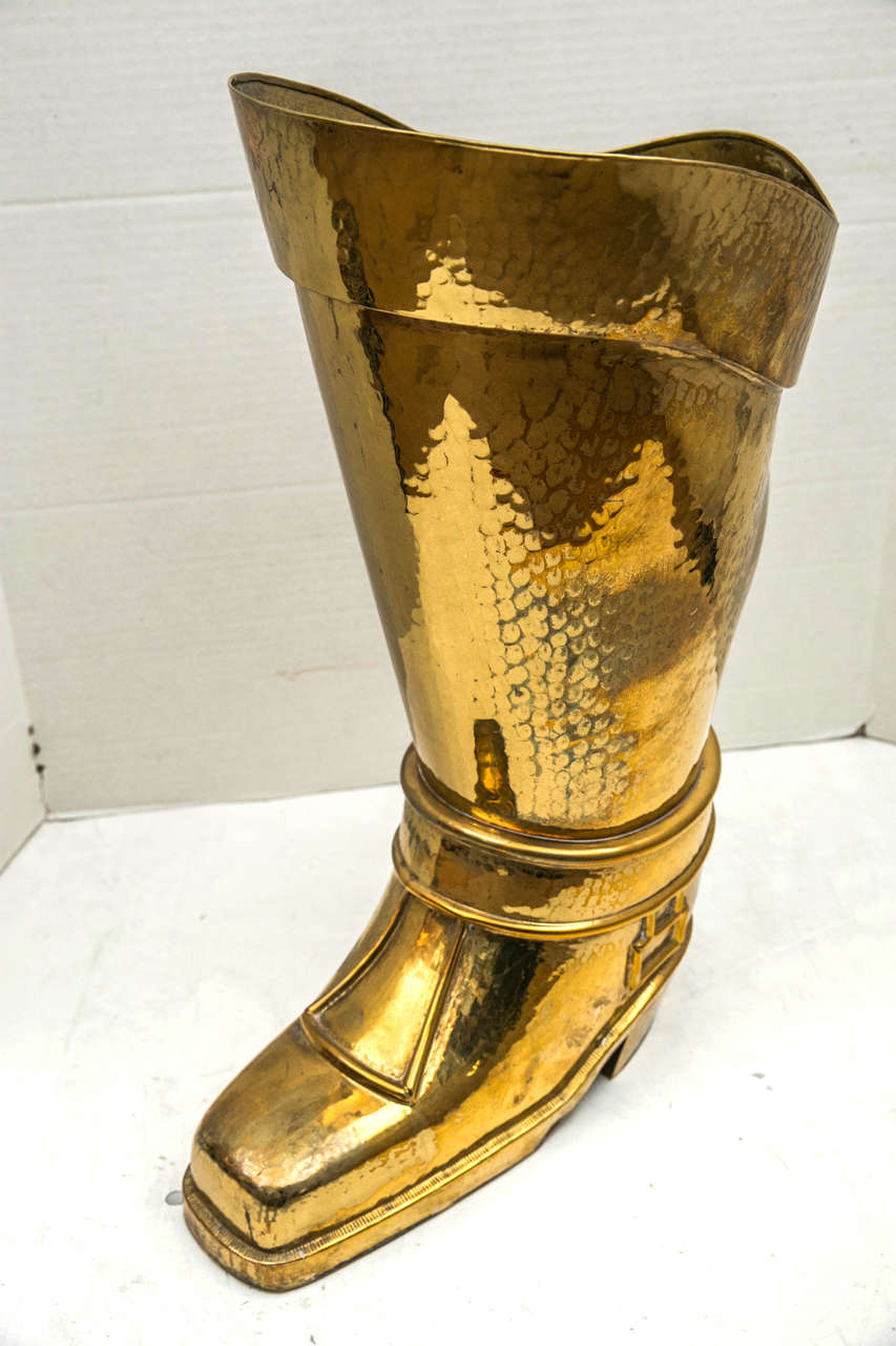 A mid 20th Century French hammered brass umbrella stand in the form of a horseman's boot.