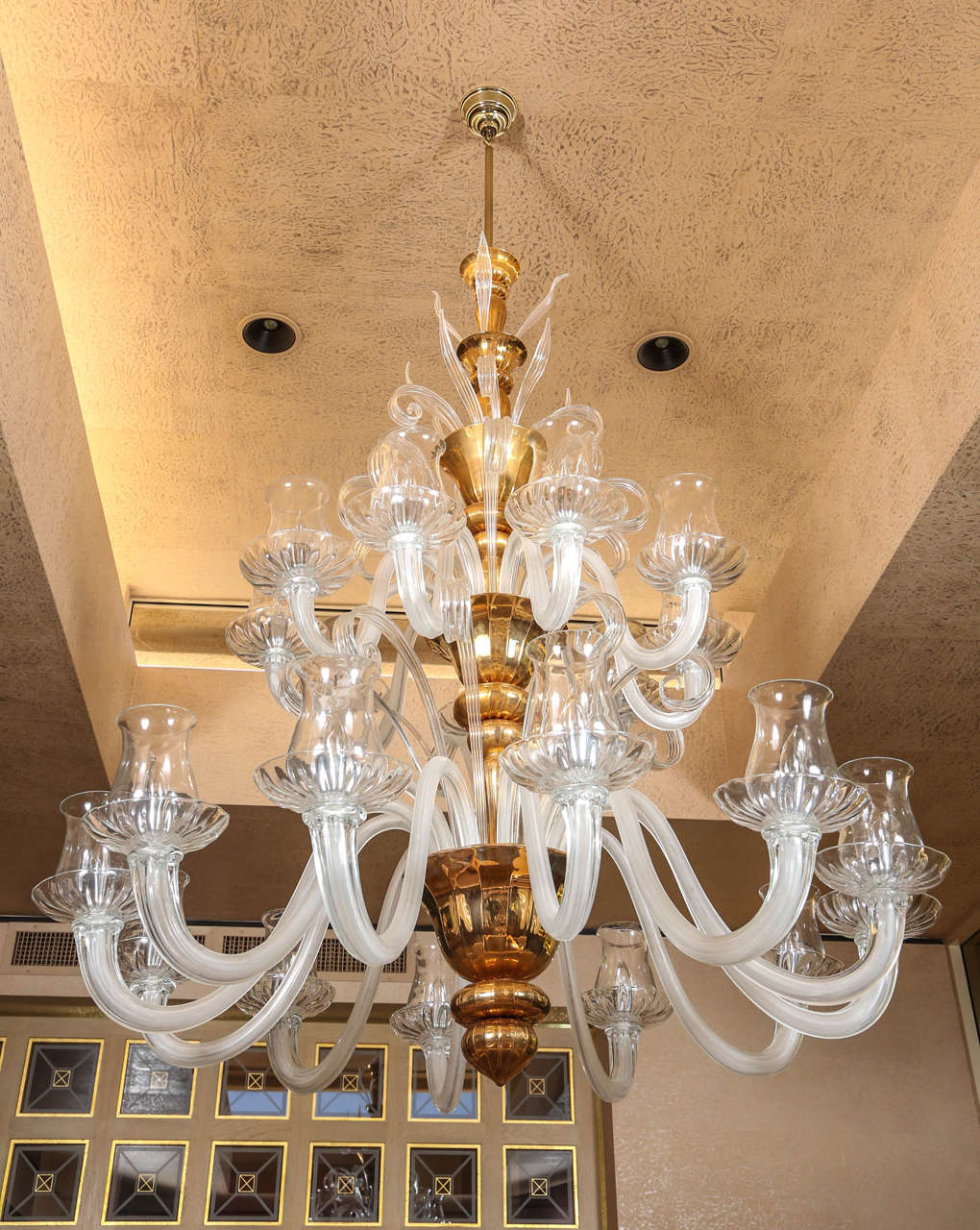 Truly stunning grand two-tier Venetian chandelier. The chandelier is elegantly accented with a gold centre armature which supports twenty-one-light sources.