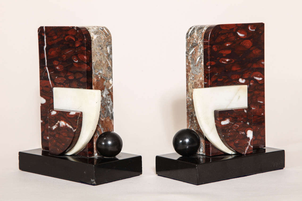 Geometric marble design in red and white marble with black patinated metal sphere on black marble base