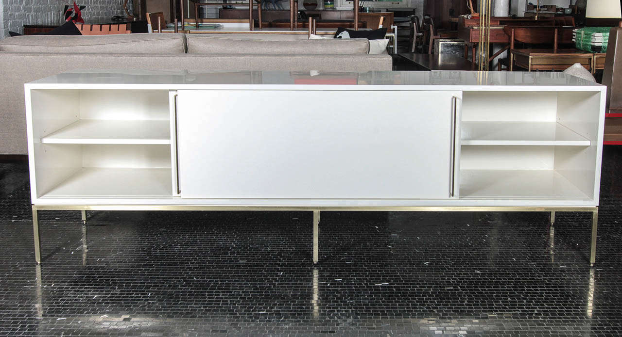 Mid-Century inspired credenza series from reGeneration.  Available in a range of colors, on brass, satin stainless steel or powder coated bases. Email for a current list of in stock colors.