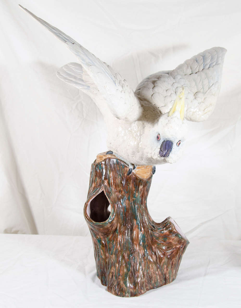 A large antique porcelain sculpture of a cockatoo made by Royal Worcester Porcelain in the last quarter of the 19th century. The sculpture is the size of a live cockatoo. Modeled as if it is about to take flight, the bird looks straight at the