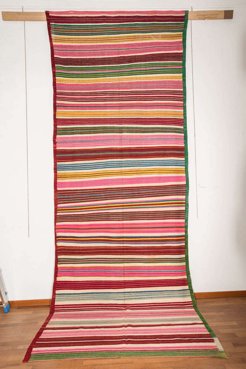 A colorful Tunisian Kilim decorated by a repeat pattern of horizontal stripes arranged in clusters of different width and palette. A very happy piece celebrating the arrival of Spring!