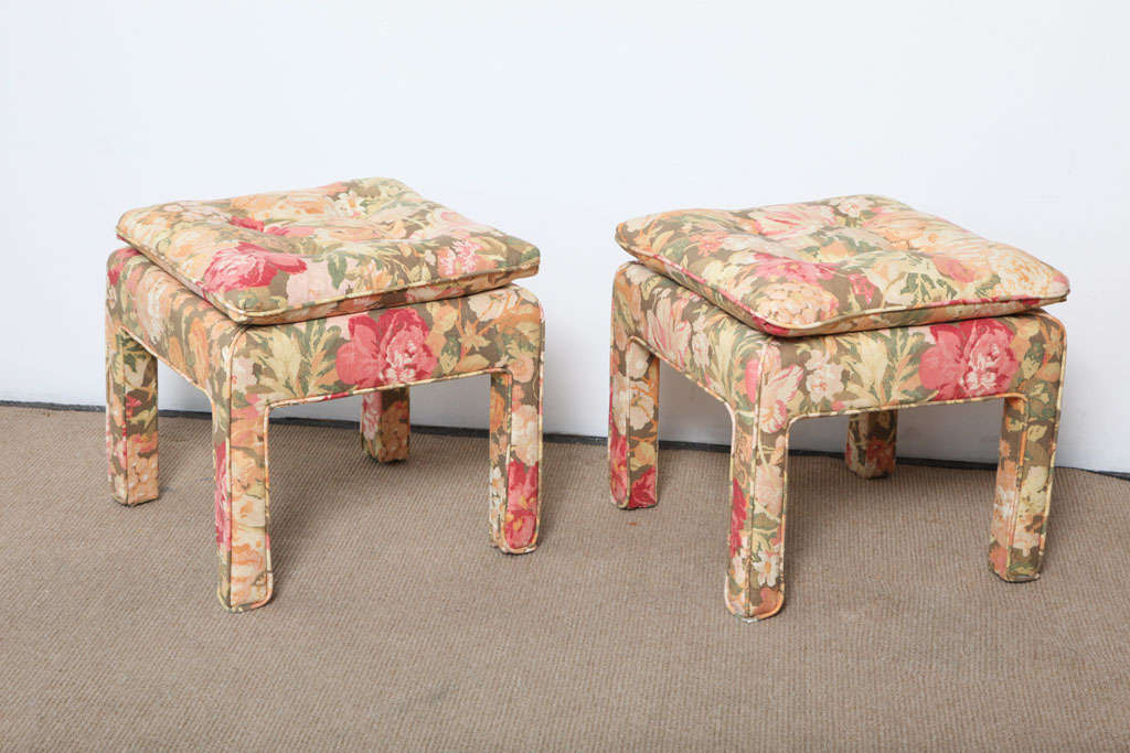 Pair of beautiful square ottomans. Covered in a floral pattern fabric. The cushioned top makes them extremely comfortable.  Perfect for any room that needs a dash of color.