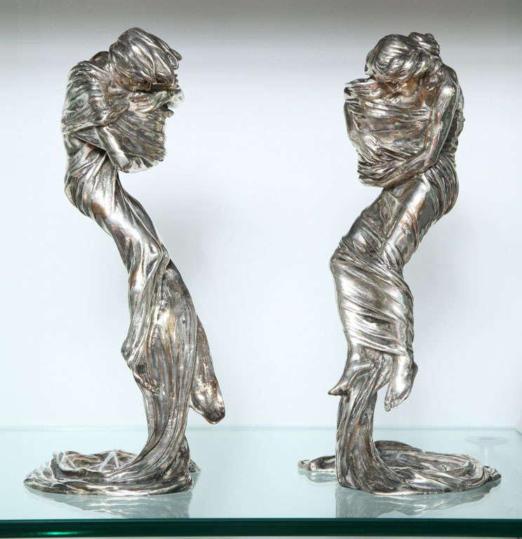 A pair of figural gilt bronze candlesticks