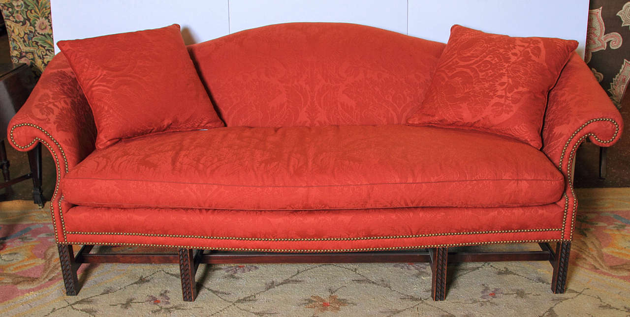 Early 20th century Chippendale style camel back sofa upholstered in red wool damask with nail-head trim.  (Re-furbished).  Front legs are carved.  Three pillows.