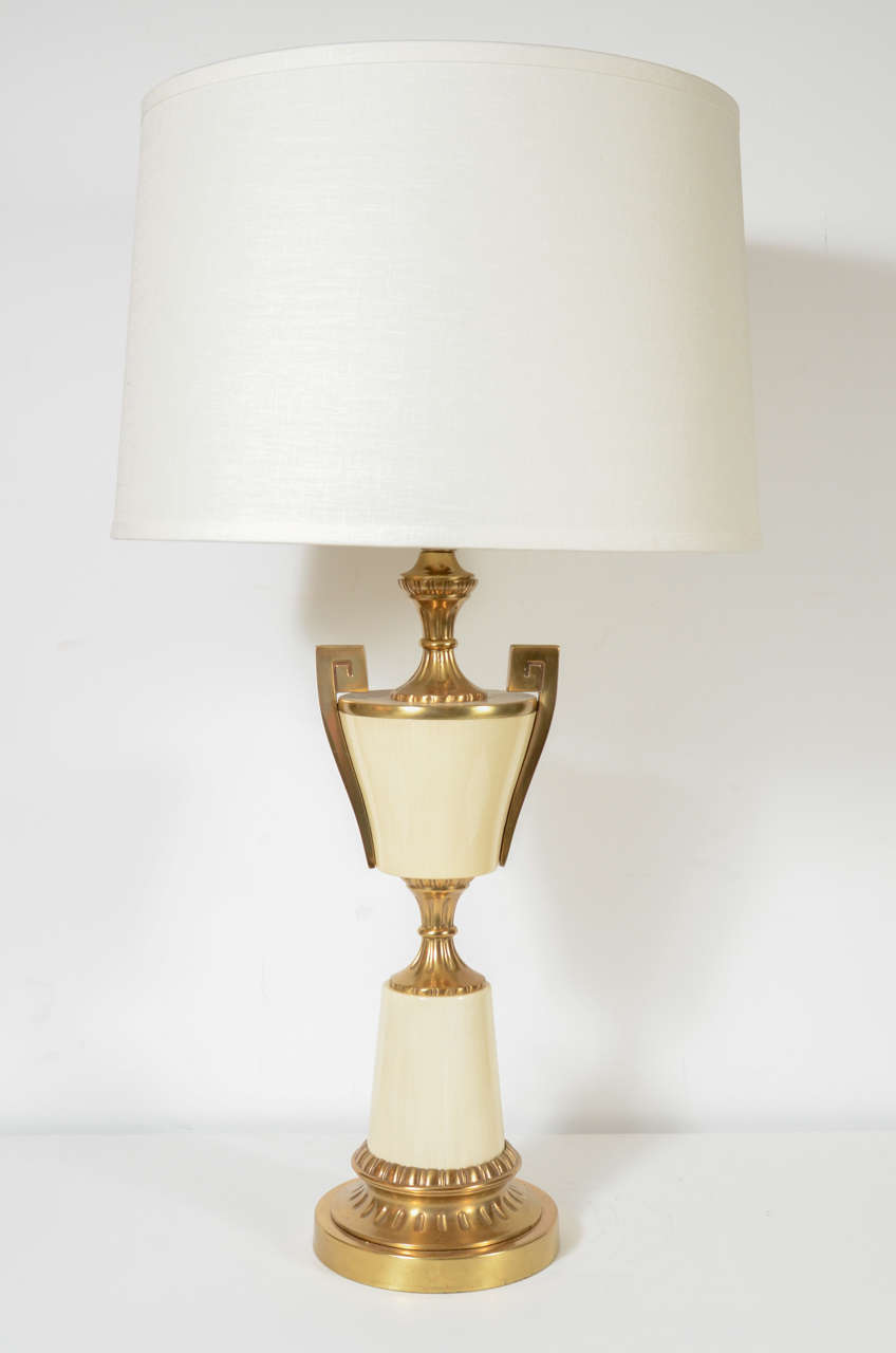 This elegant pair of Mid Century Modern table lamps were realized in the United States circa 1950. They feature cream enamel hour glass form bodies with greek key motifs flanking their shoulders as well as a reeded central embellishment that