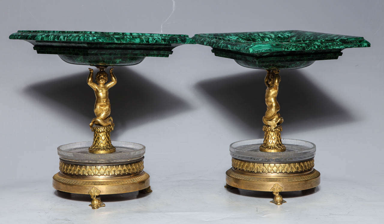 A magnificent pair of Russian Empire Period malachite, French doré bronze and cut crystal Tazzas, signed THOMIRE A PARIS. The square malachite bowls are upheld by putti (cupids) standing on tree trunks. The lower levels are formed by cut crystal