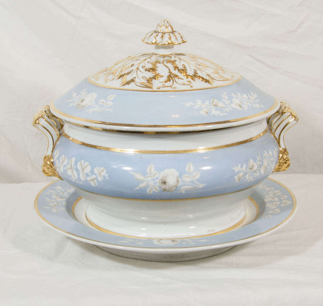 """A fine pale blue, early 19th century, Worcester soup tureen and stand painted with grisaille roses and outstanding lush gilding on the cover, finial, and handles. Marked """"Chamberlain's Worcester No 155 New Bond Street London""""."""