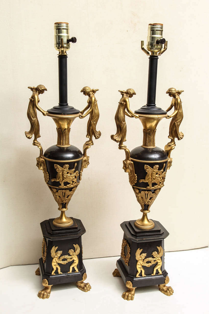Pair of Russian empire style patinated and gilt bronze figural lamps with paw feet