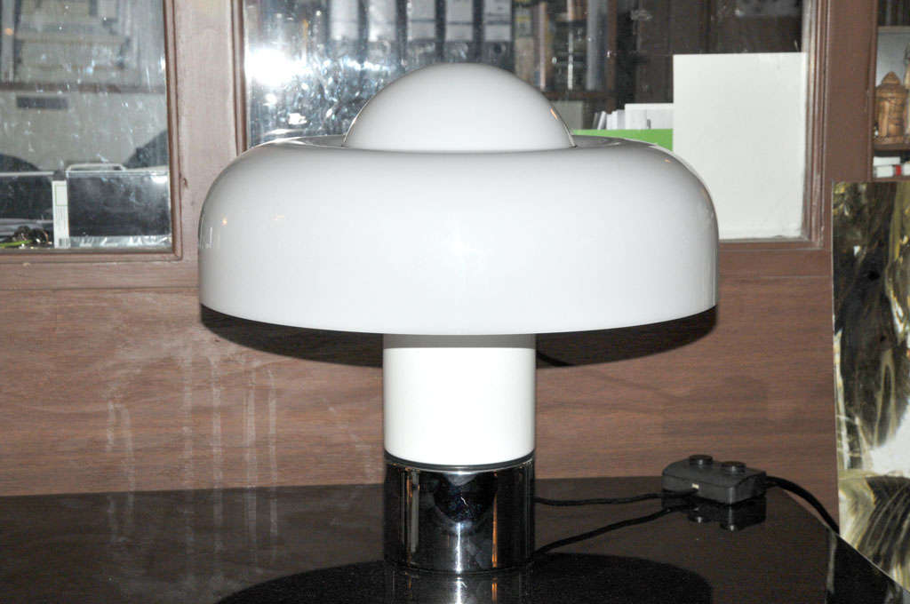 Wonderful tablelight by Italian manufacturer Guzzini, designed by Luigi Massoni in 1972. This is the rare all-white version of this table lamp. It has 4 lightsources, the top and sides of the shade can be lit in different light intensities. Price is